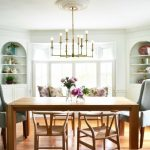 Transitional Dining Room Built In Corner Cabinets With Curve Tops Two Sloping Arm Chairs Two Wishbone Chairs Wood Dining Table Medium Toned Hardwood Floors Monochromatic Draperies Classic Chandelier