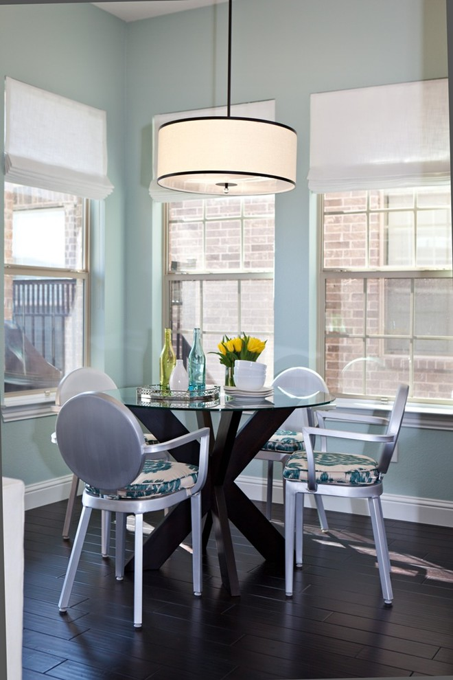 transitional dining room idea modern French style dining chairs with flower motifs upholstered seating solid blalck round top dining table black finished floors light blue walls with glass windows
