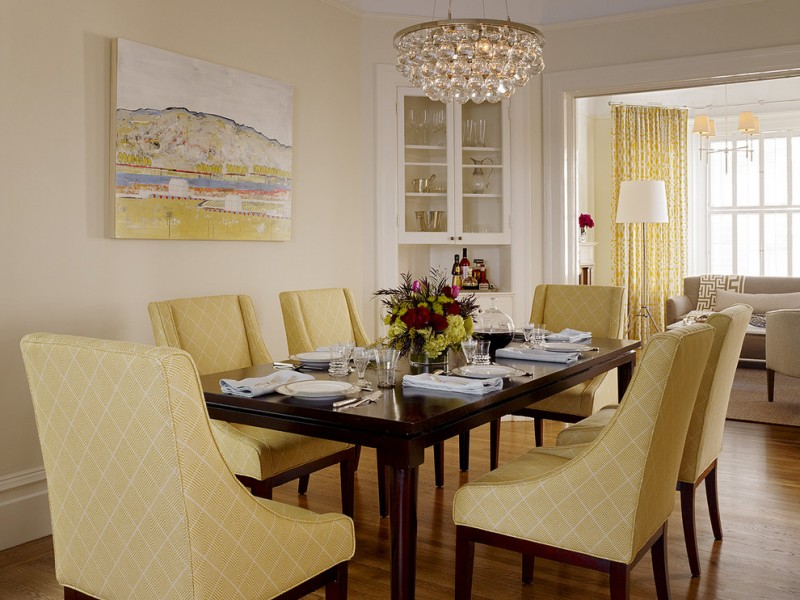 transitional dining room yellow dining chairs dark finishing wood dining table light yellow walls built in corner cabinets in white crystal chandelier yellow draperies medium toned wood floors