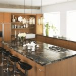 trendy kitchen design with a farmhouse sink, flat panel cabinets, medium tone wood cabinets and laminate countertops black stool white appliances