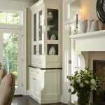 White Built In China Cabinet With Glass Door Standard Fireplace With Decorative Porcelain Pieces Dark Toned Wood Floors