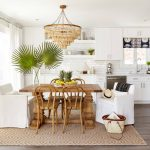 White Flat Panel Cabinet Wooden Chandelier Tiled Backsplash White Arm Chair Wooden Dining Space Area Rug Palm Leaves Wooden Floor