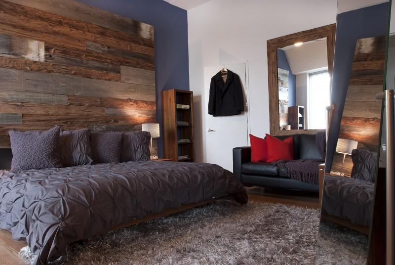 wooden wall grey wall grey bedding floor mirror framed mirror area rug wooden floor book shelves