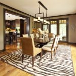 Contemporary Enclosed Dining Room Idea With Beige Walls And Medium Tone Hardwood Floors Zebra Striped Rug Pendant Lamp Animal Statues