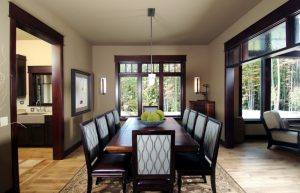 Elegant dining room with beige walls and medium tone hardwood floors wooden dining room table set in dark color accent cream rug