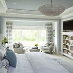 Expansive elegant master bedroom with carpet and blue walls gray sofa and pillow throws chandelier lamp geometric curtains wall mounted TV
