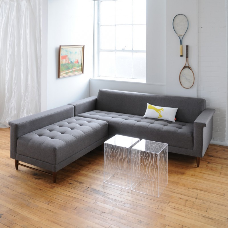L shaped sectional sofa in grey with tufted upholstery square shaped clear acrylic coffee tables with white lines decorations