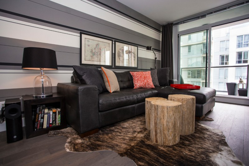 black leather sofa colorful accent pillows a cluster of tree trunk coffee tables cowhide area rug dark toned wood boards floors black finished side tables with under bookshelf
