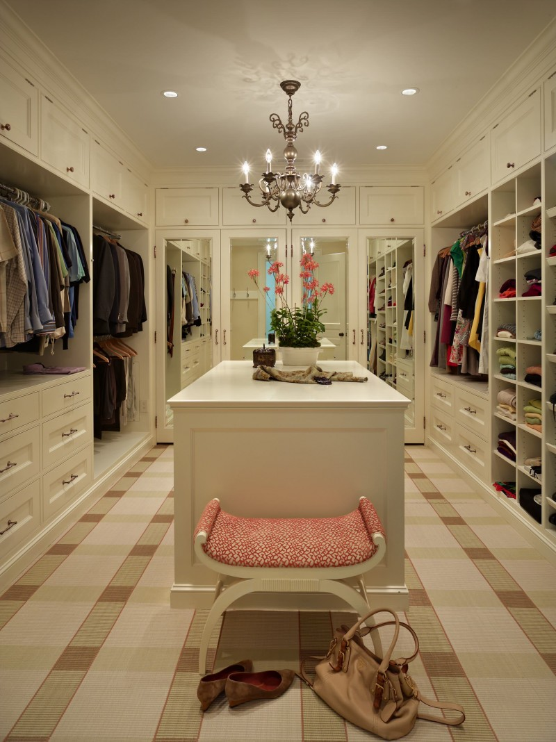 built in cabinet closet bench closet island carpeted floor open shelves drawer upper cabinet storage chandelier recessed lights