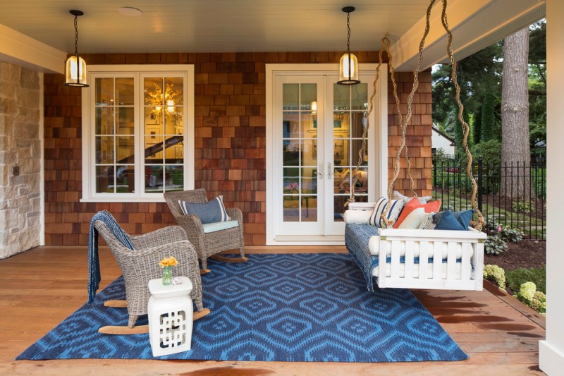 coastal style front porch hanging swing daybed in white multicolored accent pillows rattan chairs blue rug with motifs small side table in white