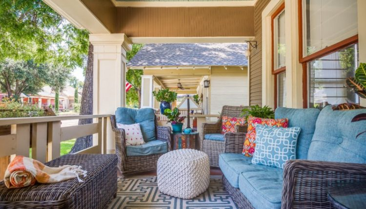 craftsman front porch dark rattan furniture set with blue comforters multicolored accent pillows white Ottoman table modern area rug