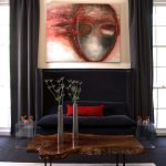 Deep Blue Sofa With Bright Red Accent Pillow Dark Toned Tree Trunk Table With Black Wrought Iron Legs Clear Acrylic Side Tables Grey Area Rug Artistic Painting