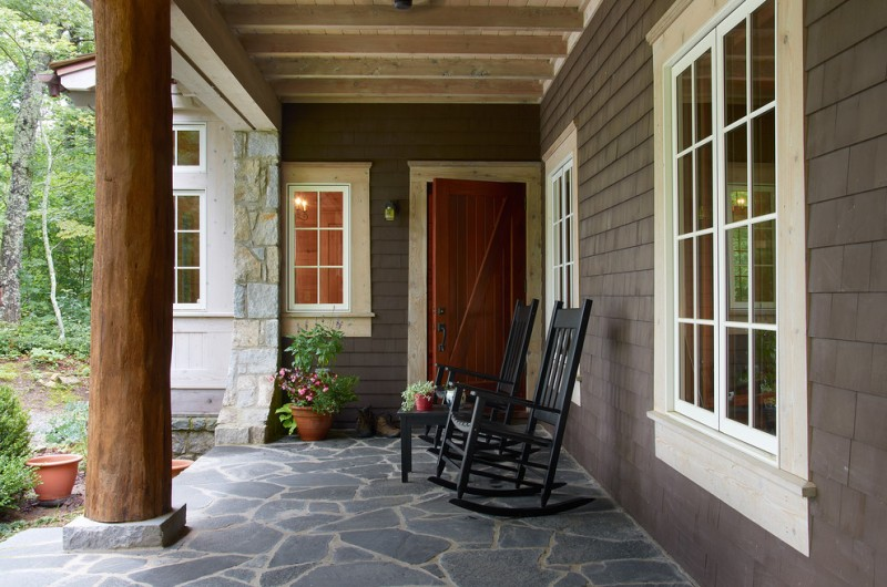 farmhouse front porch black rocking chairs solid black siding walls natural stone pavers trunk exterior pillars