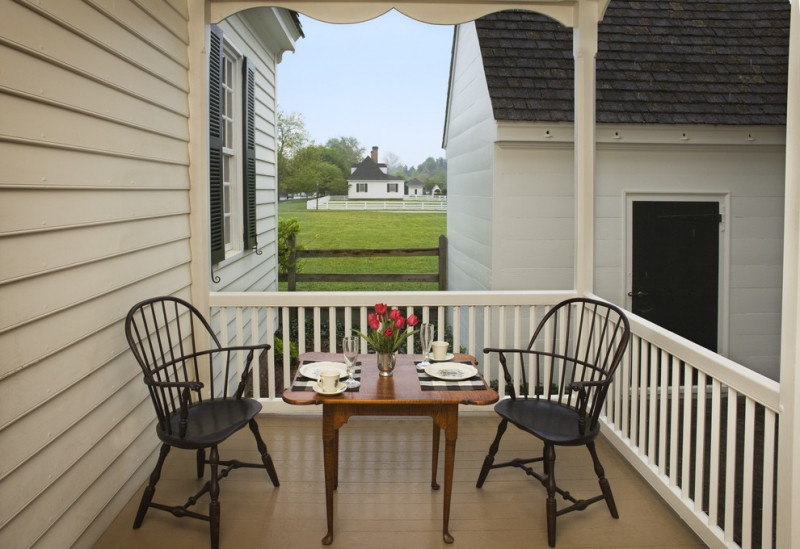farmhouse front porch idea white exterior white railing system two black chairs higher legs center table with dark wood finishing