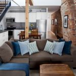 Grey L Shaped Sectional Sofa Blue Accent Pillows Dark Toned Wood Coffee Table Red Brick Walls Wood Interior Pillar Wood Floors Without Finishing