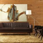 Mid Century Living Room With Modern Appeal Dark Brown Leather Sofa With Tuftings A Pair Of Dark Brown Chairs With Dark Wood Cross Legs Light Brown Area Rug Wood Siding Walls Abstract Painting