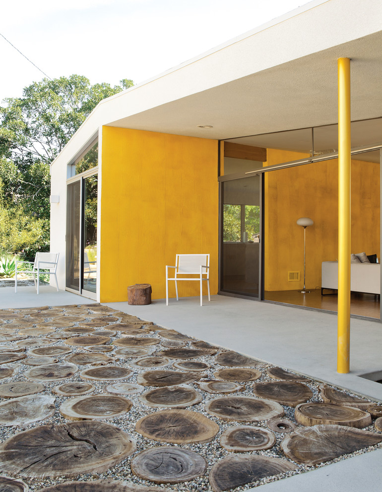mid century modern patio idea deep yellow walls and pillar white chair dark tree trunk side table white floors tree trunk pavers idea