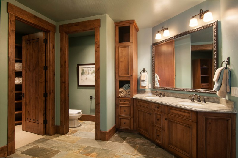 mountain style bathroom with an undermount sink, recessed panel cabinets and medium tone wood cabinets blue wall paint ceramic tiles sconces above mirror