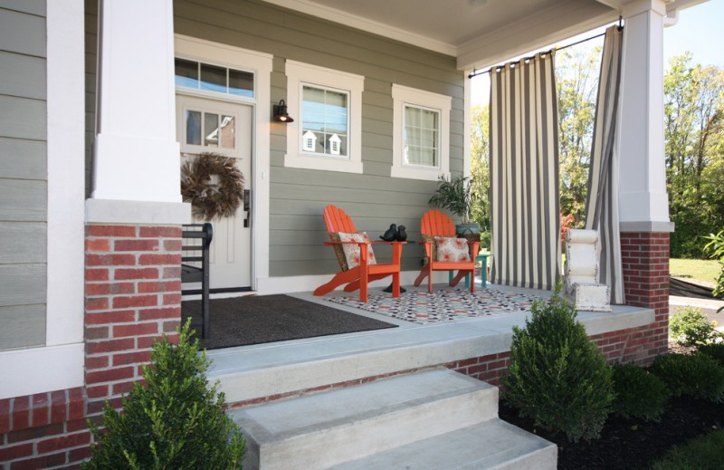 orange crafstman style chairs for front porch multicolored mosaic tiles floors grey wood siding exterior walls white trimmed exterior windows white trimmed entrance door