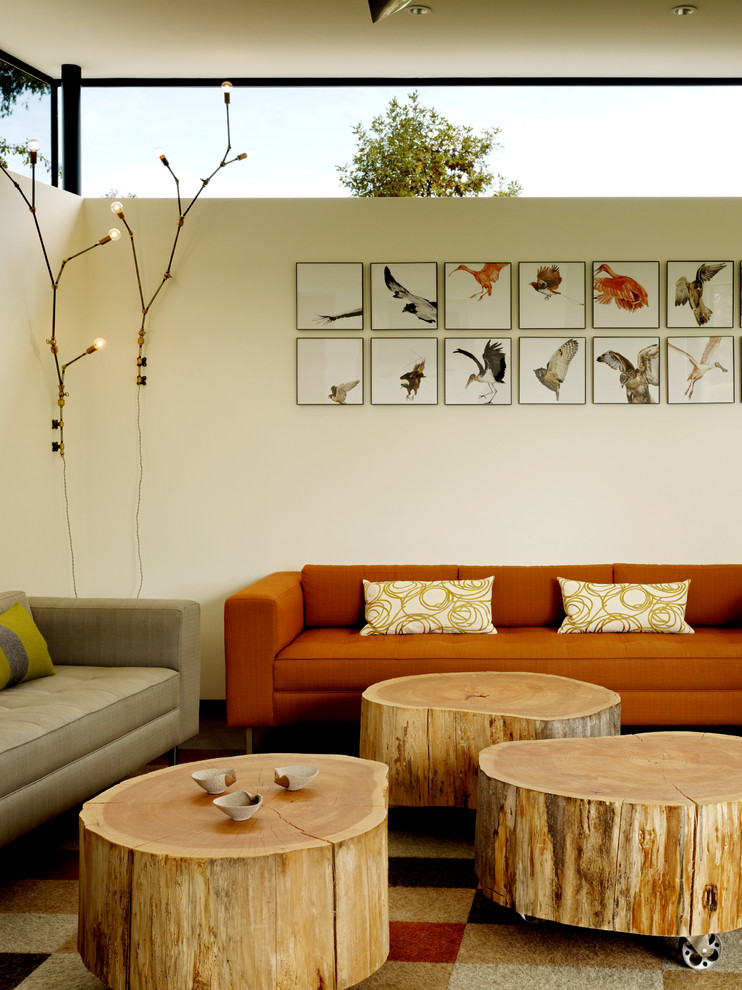 orange sectional sofa beige accent pillows cluster of tree trunk coffee tables modern area rug with modern motifs