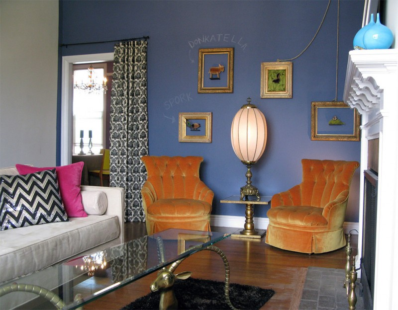 orange velvet chair slipcovers light grey sofa with accent pillows bold blue walls colorful window curtains
