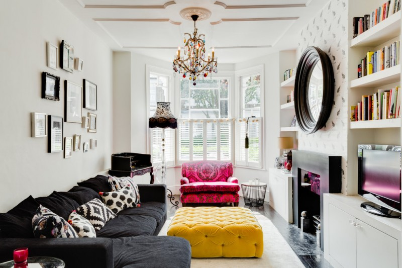 small living room with black corner sofa, yellow square ottoman for coffee table, red couch, white rug, mirrors, colorful glass chandelier