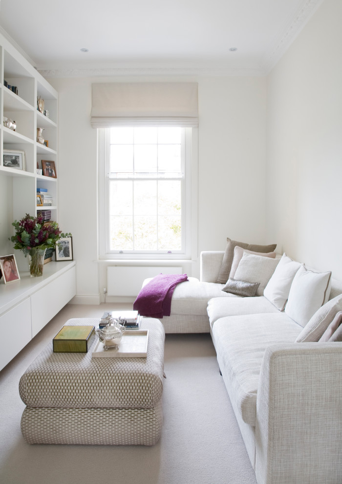 small living room with white long sofa with white pillows, white rug, white ottoman for coffee table, white book shelve