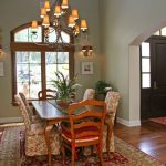 timeless dining room with green walls and dark hardwood floors chandelier lamp wooden dining room set accent chairs and carpet