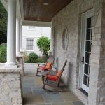 Traditional Front Porch Grey Rocking Chairs Orange Accent Pillows Natural Stone Exterior Walls Grey Tiles Floors Dark Toned Wood Boards Ceilings