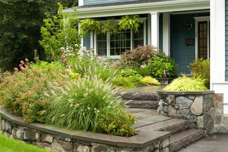 traditional front yard landscape concrete ceramic stairs pathways stone gate green shrubbery gray painted wooden deck wall glass front door and windows in white trim