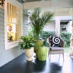Transitional Front Porch Idea Bright Toned Rattan Chair Monochromatic Throw Pillow Green Side Table Green Vase White Vase Glossy Black Wood Board Floors