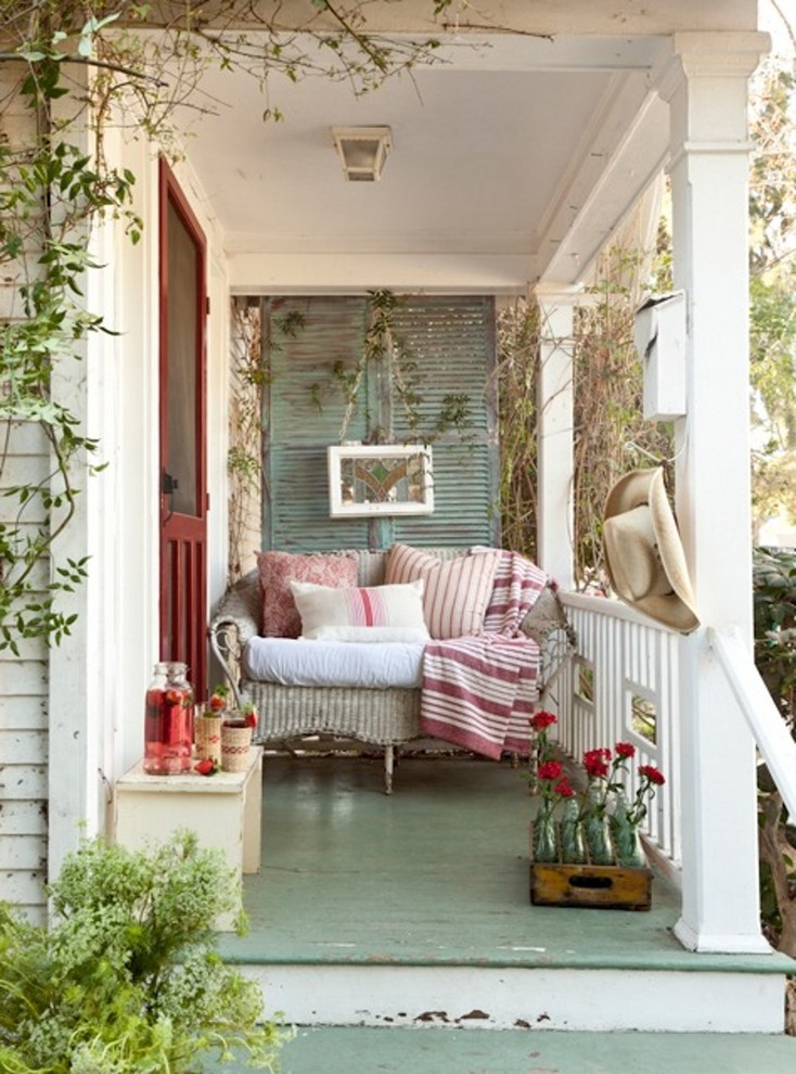 vintage inspired front porch a single sofa with dominant pink accent pillows light blue laminate floors shabby blue back red entry door white bench for side table