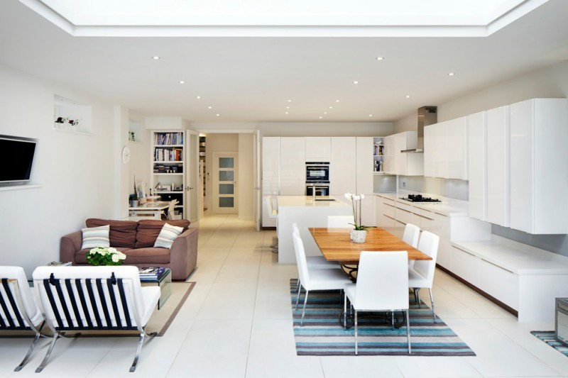 contemporary combo room with living area with white and brown chairs and brown rug, dining area with wooden table and white chairs, with blue stripped rug