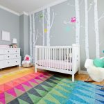 nursery with grey painted wall with white artwork of trees and owls, white wooden cribs, white wooden crib, white chair, white floor lamp, colorful triangle patterned rug