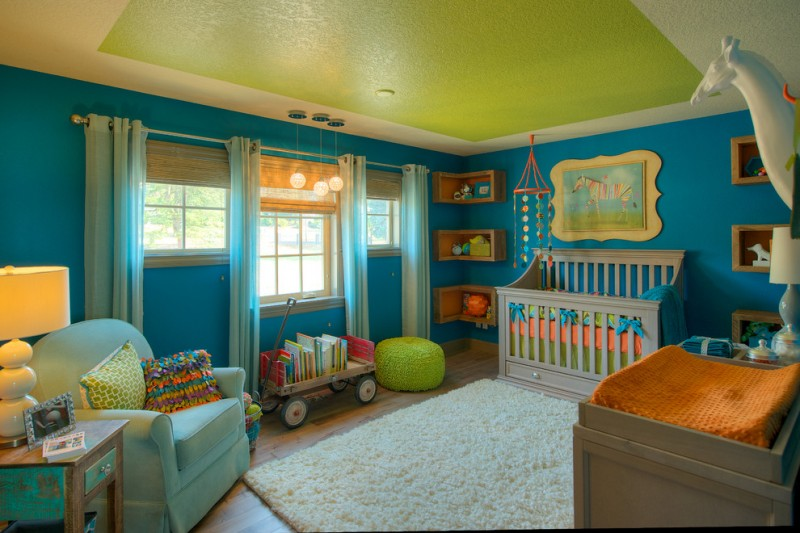 nursery with ocean blue wall, white curtains on three windows, soft blue comfortable chair, wooden side table, table lamp, wooden flooring, soft peach rug, corner shelves