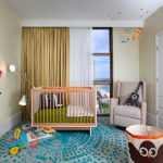 nursery with soft beige wall, soft grey rug with blue pattern, light brown crib, soft beige chair, wooden shelf