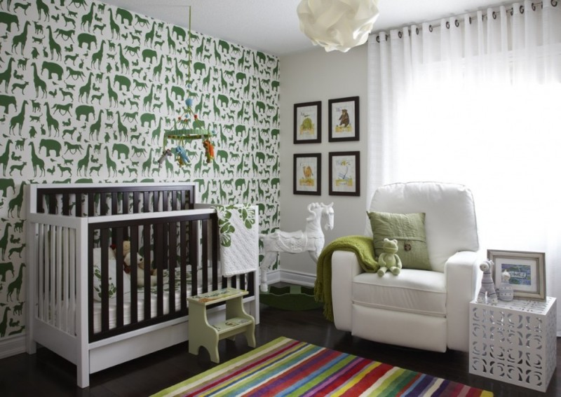 nursery with white chair, white wooden crib, dark wooden flooring, white painted wall with green animal stikers on one side, colorful lined rug