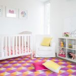 nursery with white plain wall, white wooden shelves for toys, white wooden crib, white chair, purlpe white orange colored triangle patterned rug
