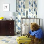 nursery with white wooden crib, brown wooden cabinet, yellow car toy, bear, blue beige white rug with round pattern, white table lamp