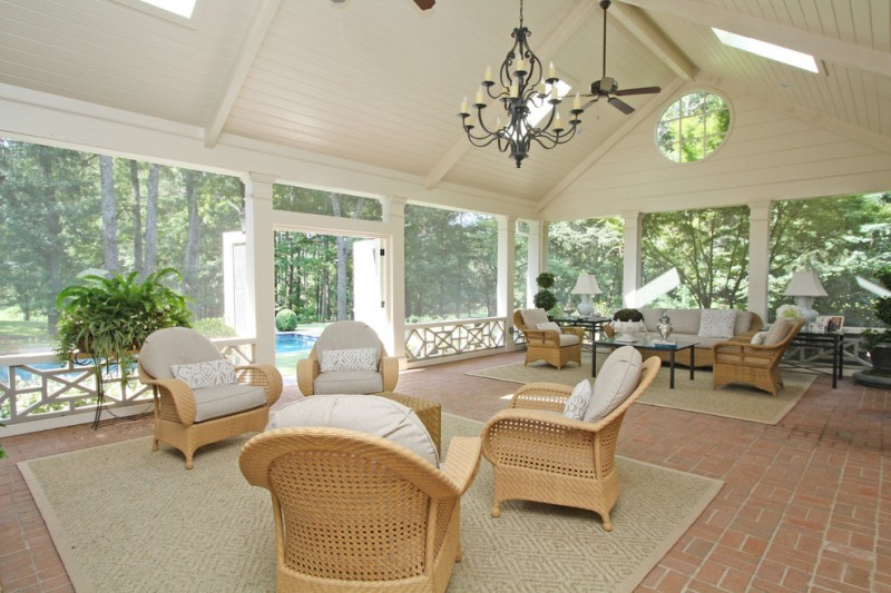 pretty white porch with grey rugm rattan chairs with white cushions, ceiling fan, chandelier, white wooden vaulted ceilng, large glass window wall with white metal f