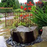 rock feature water fountain with grey river stones around