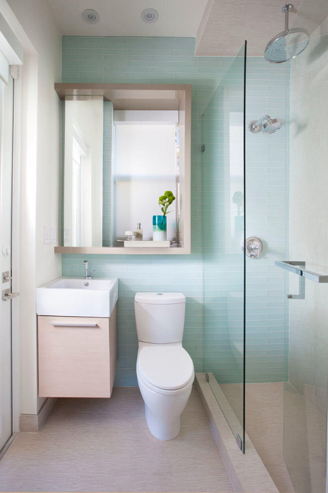 small bathroom with pale blue tiles wall, beige flooring, white toilet, wooden cabinet with white sink on top, mirror