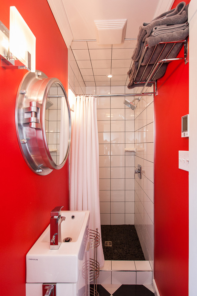 small bathroom with red walls, white tiling walls in shower area, black and white flooring, white sink, round mirror