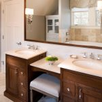 small sink with brown wooden cabinet, whte marble top, make up counter in the middle of two sinks,