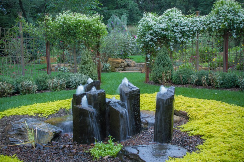 tall black rock features water fountain in the middle of a garden