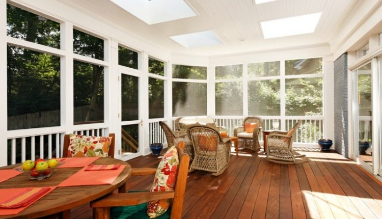 traditional porch with brown wooden flooring, white wooden ceiling with glass window ceiling, brown wooden dining table set. brown rattan chairs and sofa