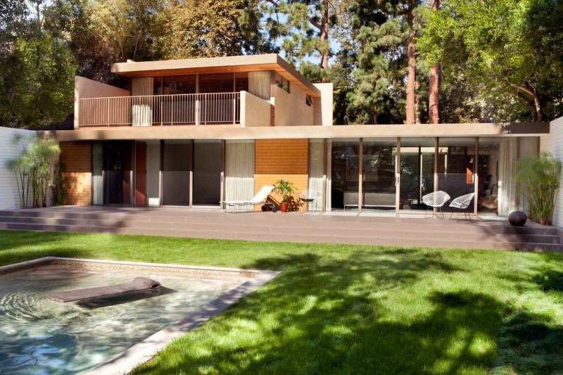 two story midcentury home with nude wall and glass wall, orange bricks, flat clean roof