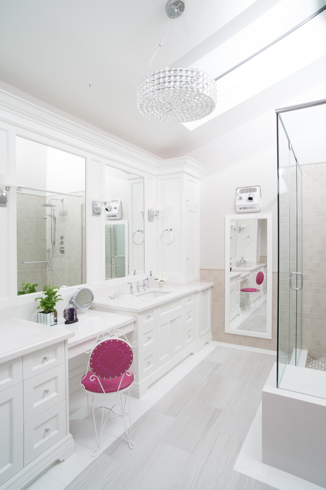 white bathroom with two white sinks and make up counter in the middle with shocking pink chair