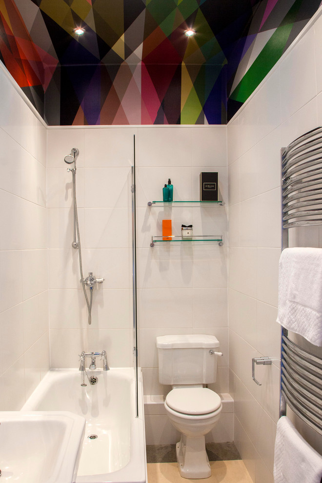 white small bathroom with colorful assymetric pattern ceiling, white toilet, white sink, white tub with showe and glass partition, glass shelves