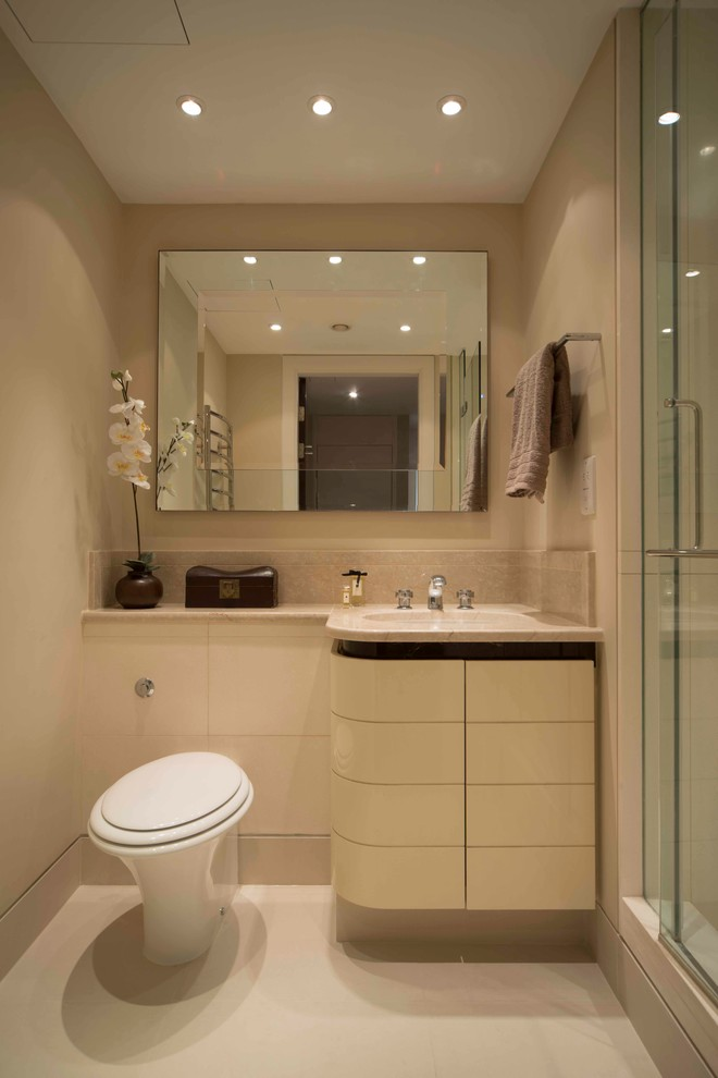 white small bathroom with white toilet, cream wastafel top and sink, square mirror, shower area with glass door